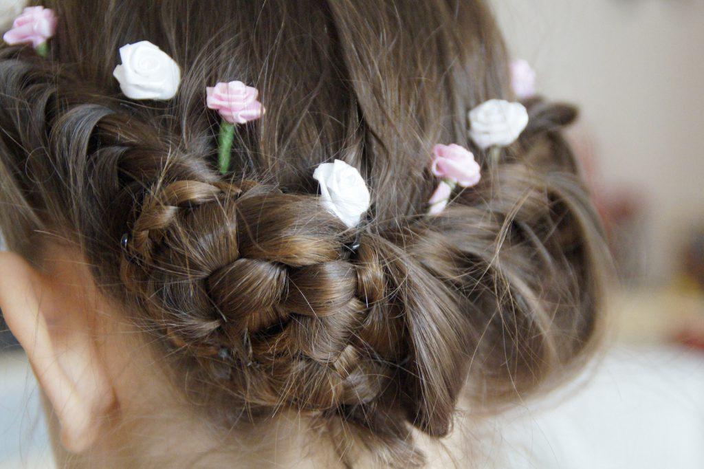 Coiffure d'une petite fille avec de jolies fleurs et des tresses.